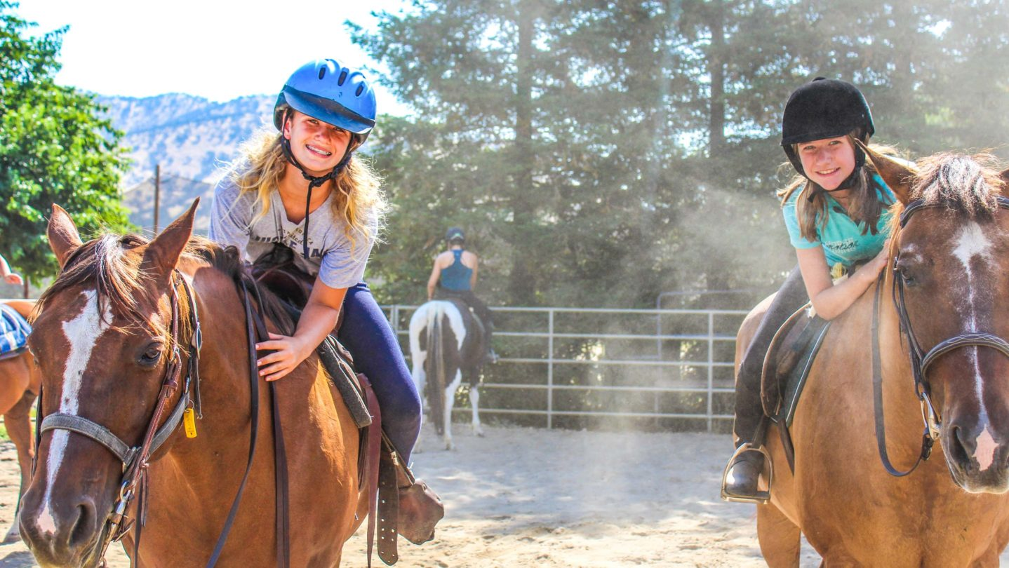 Campers smiling while riding horses