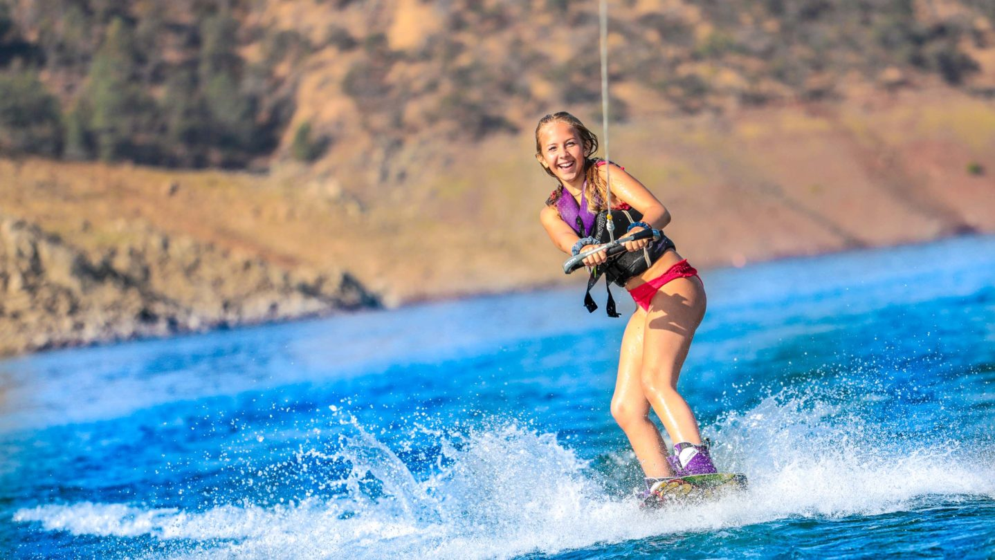 A camper learning how to waterski and smiling