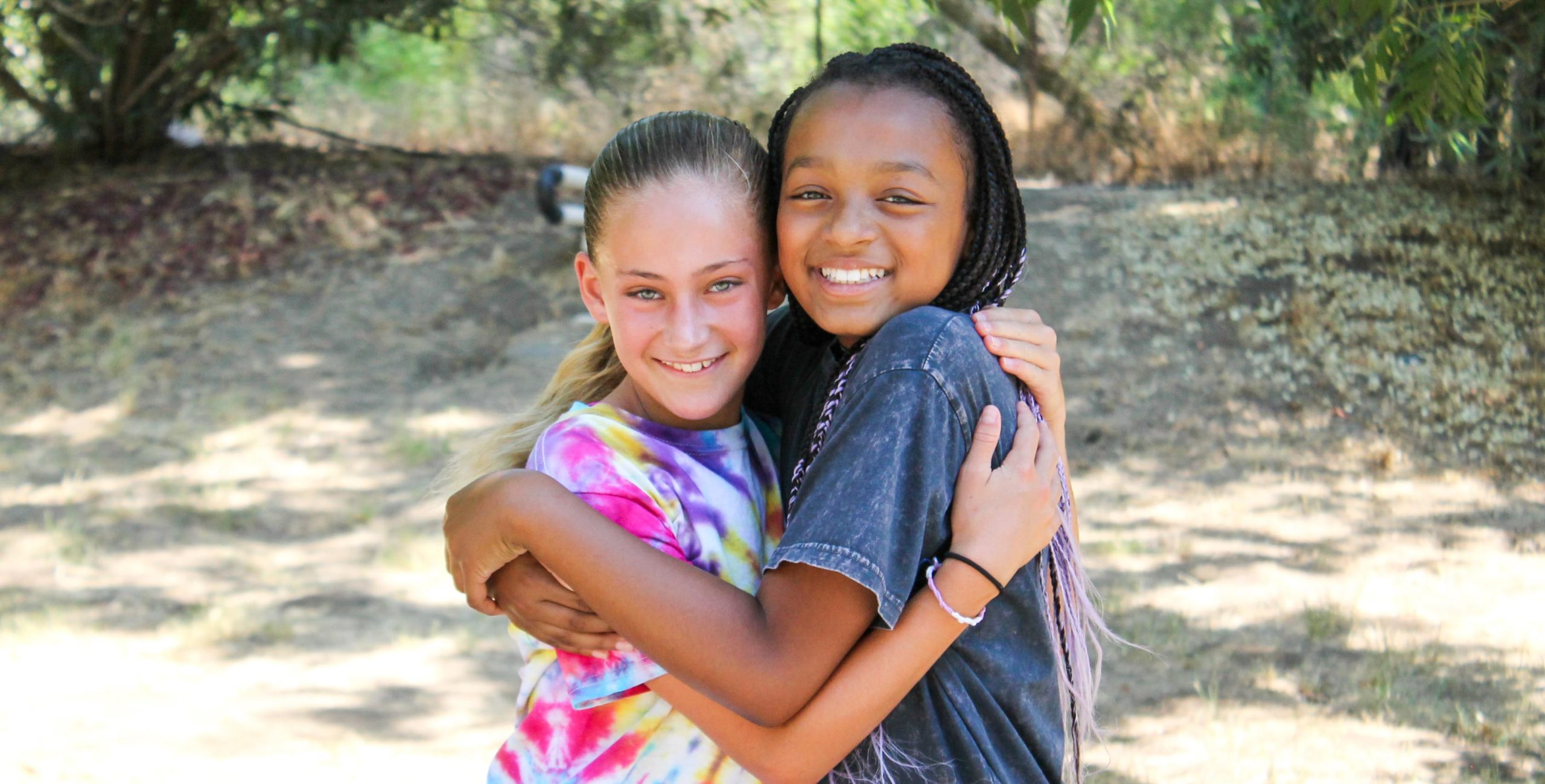 Campers hugging and smiling at the camera